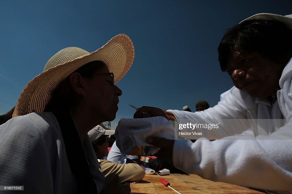 People receive the communion during a mass for the people at Ecatepec on February 14, 2016 in Ecatepec, Mexico. Pope Francis is on a five days visit in Mexico from February 12 to 17 where he is expected to visit five states.