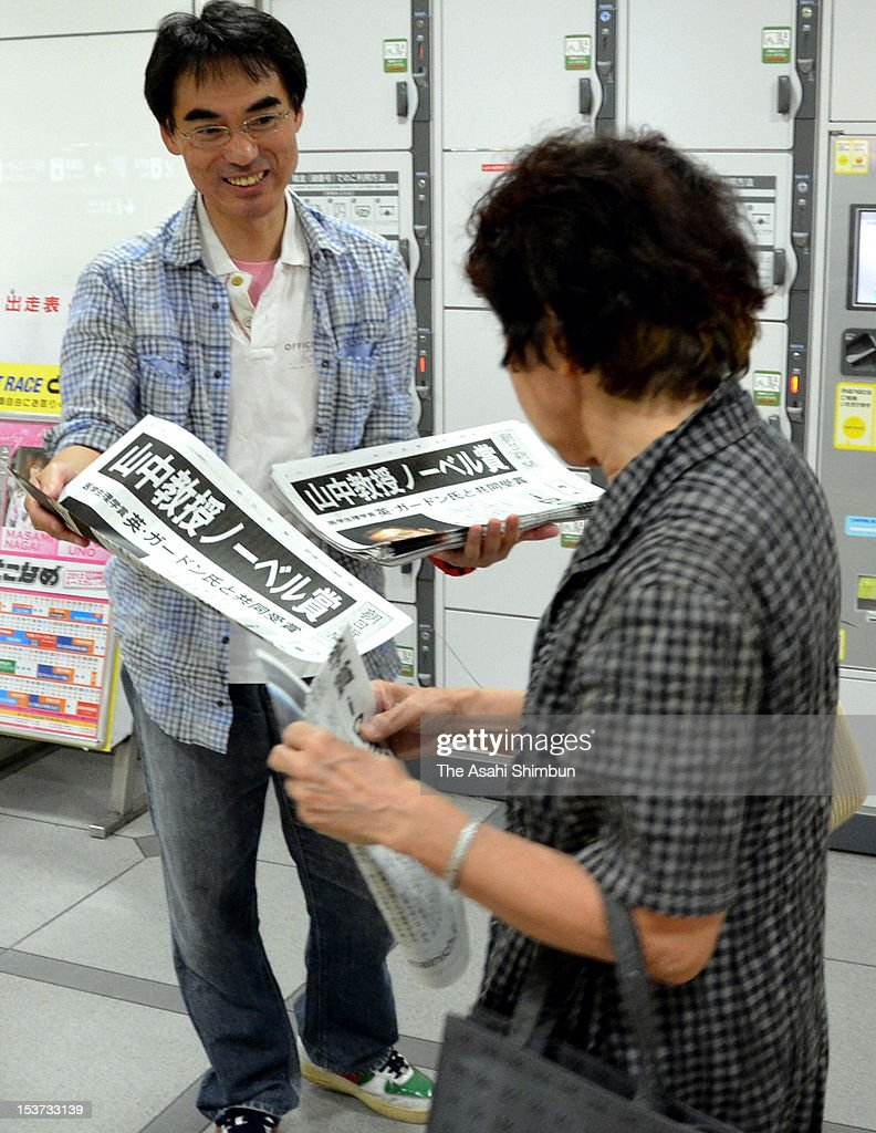 People receive the extra edition of newspapers distributed to celebrate Kyoto University professor Shinya Yamanaka winning the Nobel prize at Nagoya station on October 8, 2012 in Nagoya, Aichi, Japan. Yamanaka and Sir John Gurdon have both been awarded the Nobel prize for medicine or physiology for their work as pioneers of stem cell research.