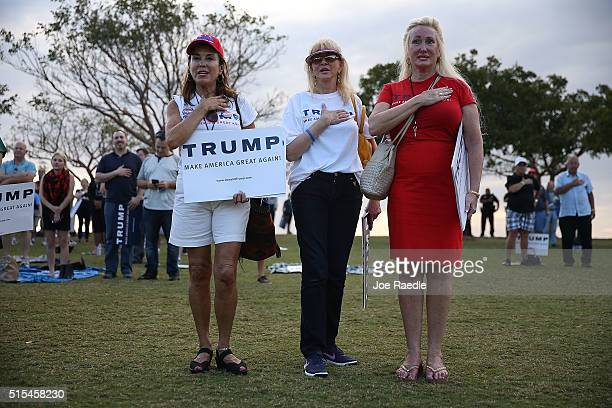 People recite the Pledge of Allegiance as they wait for the arrival of Republican presidential candidate Donald Trump during his campaign rally at...