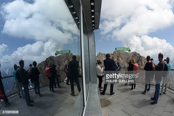 People reflect in a window as they watch activists of the ecologist Green party standing in front of the summit cross of the Zugspitze mountain near...