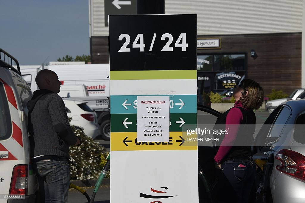 People refuel their cars in a petrol station where a posted sign reads 'Rationing, 20 litres per vehicle, jerricans forbidden, prefectoral decree of Ile et Vilaine of May 20 2016' in Combourg, western France, on May 24, 2016, following blockades of several oil refineries and fuel depots in France by protesters opposed to government labour reforms. Petrol shortages caused long tailbacks of motorists in parts of France on May 23 as protesters angry over government labour reforms blockaded some of the country's oil refineries and fuel depots. The action was the latest in three months of strikes and protests against the reform, which has set the Socialist government against some of its traditional supporters and sometimes sparked violence. MEYER