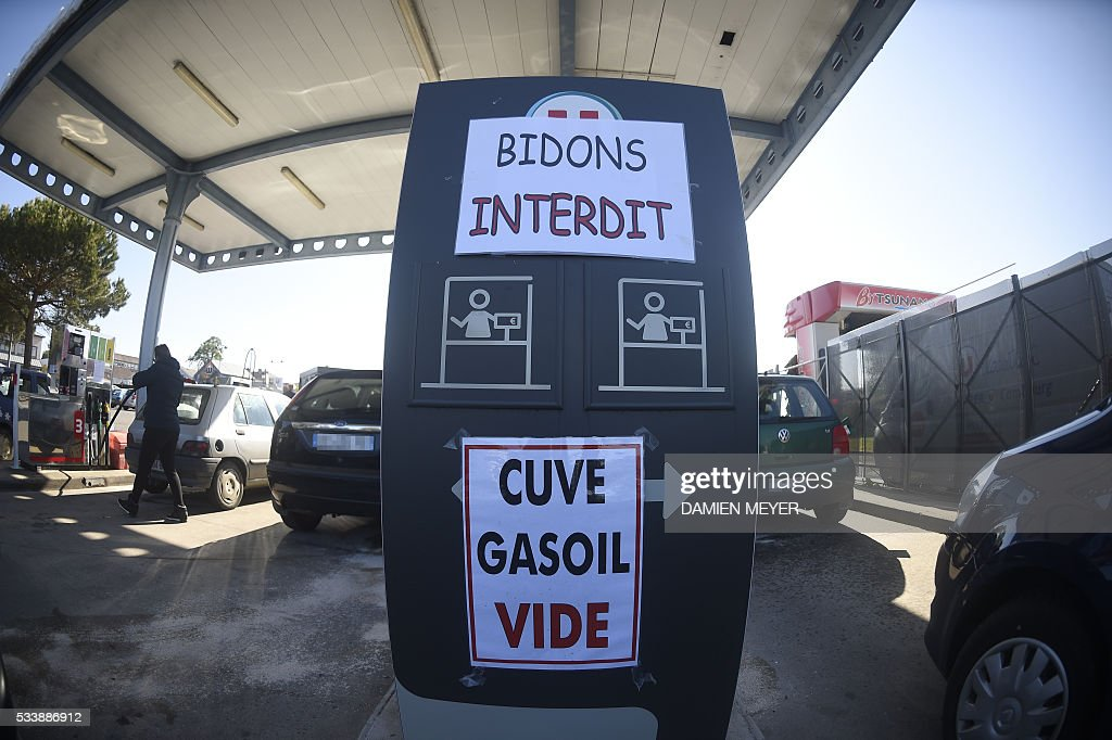 People refuel their cars in a petrol station where posted placard reads 'No jerricans ' (up) ' and 'Diesel vat empty' in Combourg, western France, on May 24, 2016, following blockades of several oil refineries and fuel depots in France by protesters opposed to government labour reforms. Petrol shortages caused long tailbacks of motorists in parts of France on May 23 as protesters angry over government labour reforms blockaded some of the country's oil refineries and fuel depots. The action was the latest in three months of strikes and protests against the reform, which has set the Socialist government against some of its traditional supporters and sometimes sparked violence. MEYER
