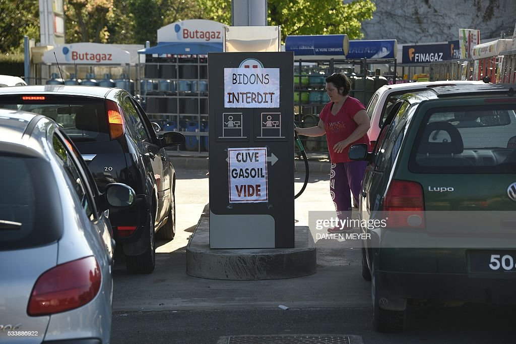 People refuel their cars in a petrol station where posted placard reads 'No jerricans ' (up) ', 'Diesel vat empty' in Combourg, western France, on May 24, 2016, following blockades of several oil refineries and fuel depots in France by protesters opposed to government labour reforms. Petrol shortages caused long tailbacks of motorists in parts of France on May 23 as protesters angry over government labour reforms blockaded some of the country's oil refineries and fuel depots. The action was the latest in three months of strikes and protests against the reform, which has set the Socialist government against some of its traditional supporters and sometimes sparked violence. MEYER