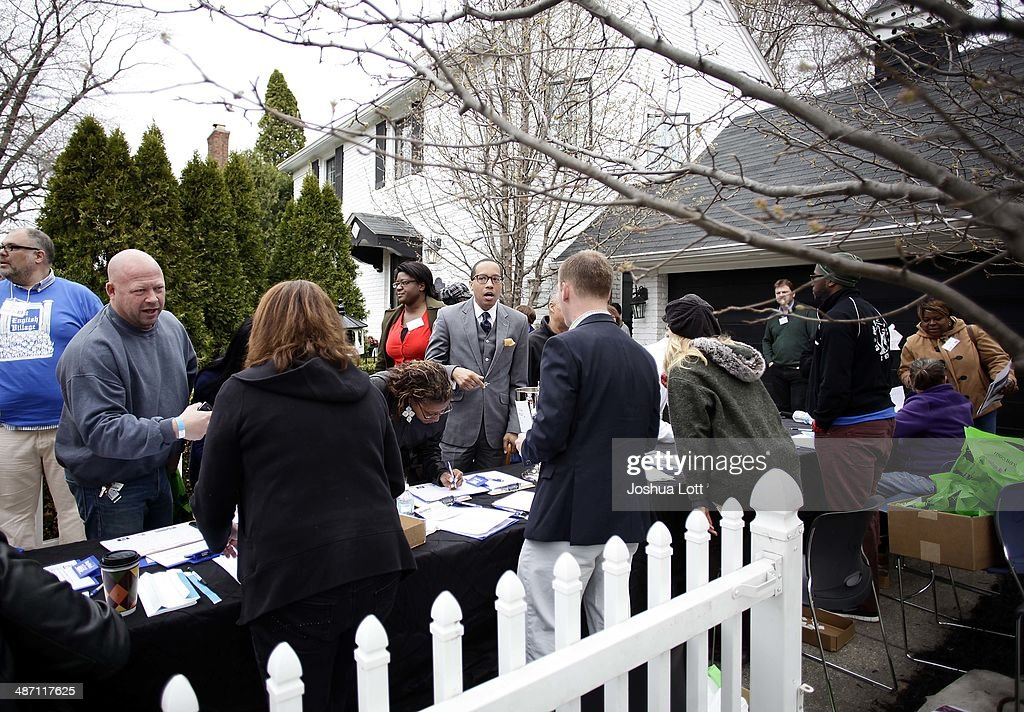 People register to tour one of twelve homes being auctioned off in the East English Village neighborhood April 27, 2014 in Detroit, Michigan. The city of Detroit and the Detroit Land Bank will auction off 12 homes starting May 5. One home will be auctioned off per day with an opening bid of $1,000.