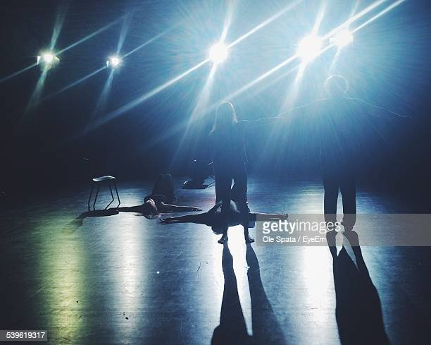 People Rehearsing On Illuminated Stage