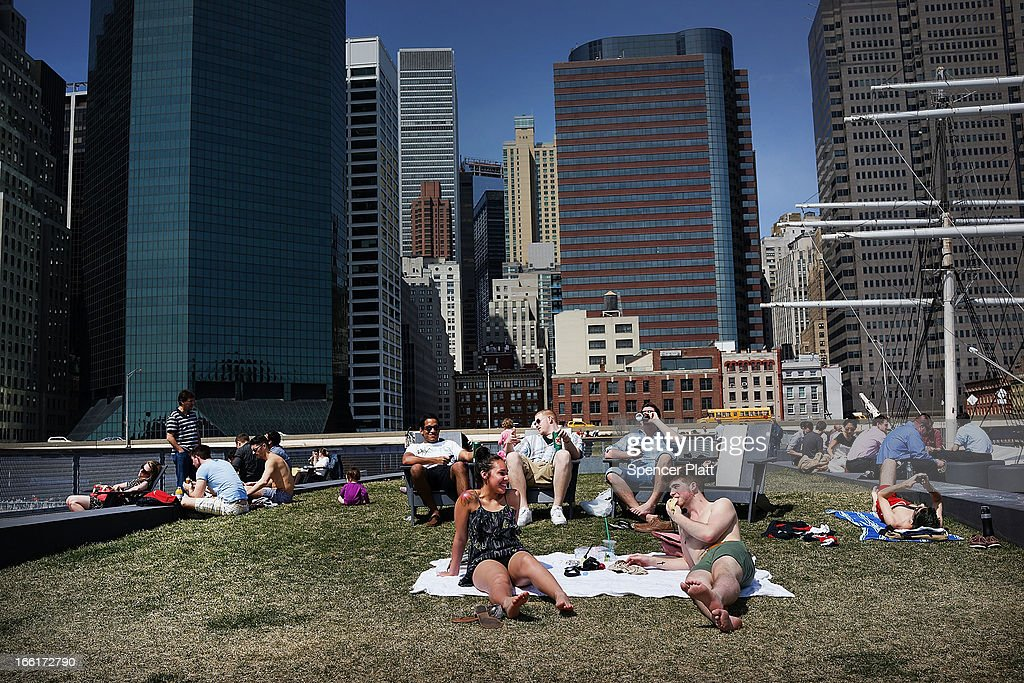People relax along the East River in lower Manhattan during warm weather on April 9, 2013 in New York City. For the first time since October, temperatures are expected to rise above 70 degrees this week in New York and surrounding areas.