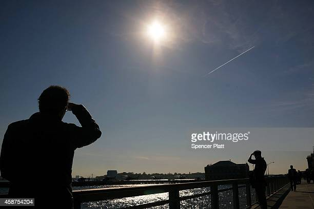 People relax along the water in lower Manhattan on a sunny afternoon which saw temperatures hit the lower sixties on November 10 2014 in New York...