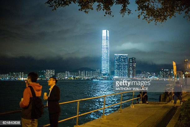 People relax along the waters of Victoria Harbour in Hong Kong on November 21 in front of a view of the brightly lit ICC building in the district of...