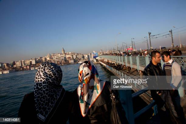 People relax at sunset on the Galata Bridge on February 20 2012 in Istanbul Turkey Though not the capital Istanbul is the cultural economic and...