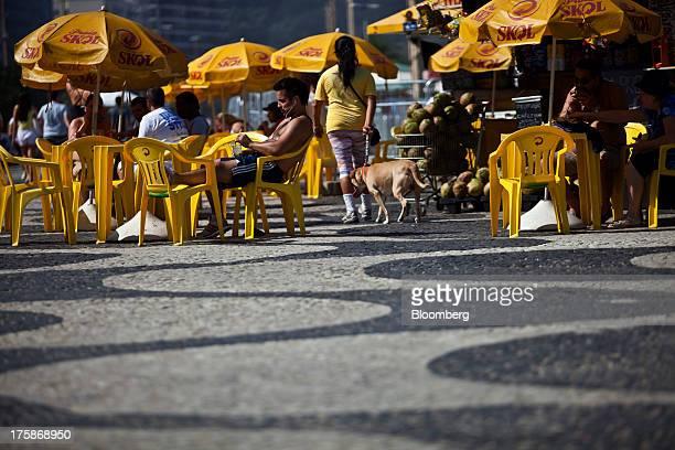 People relax at tables with umbrellas bearing the logo for Cia de Bebidas das Americass Skol brand beer at Ipanema beach in Rio de Janeiro Brazil on...