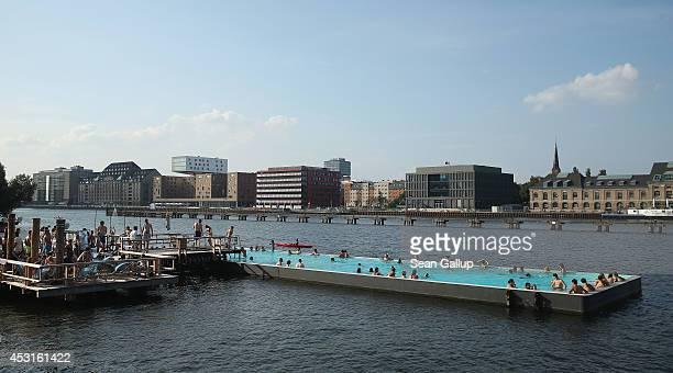People relax at the Badeschiff outdoor swimming pool which lies in the Spree River in AltTreptow district on August 2 2014 in Berlin Germany Warm...