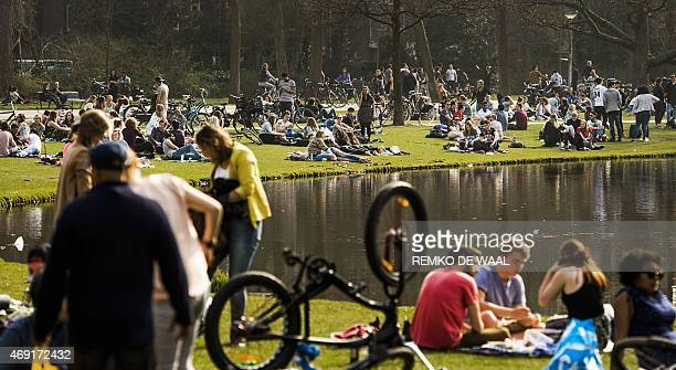 People relax at the Vondelpark in Amsterdam on April 10 2015 Parts of the Netherlands experienced the warmest day of the year so far with...