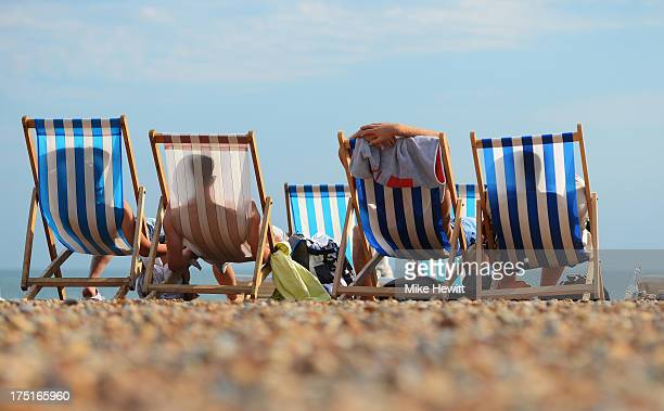 People relax in deck chairs during the hot weather on Brighton beach on August 1 2013 in Brighton England