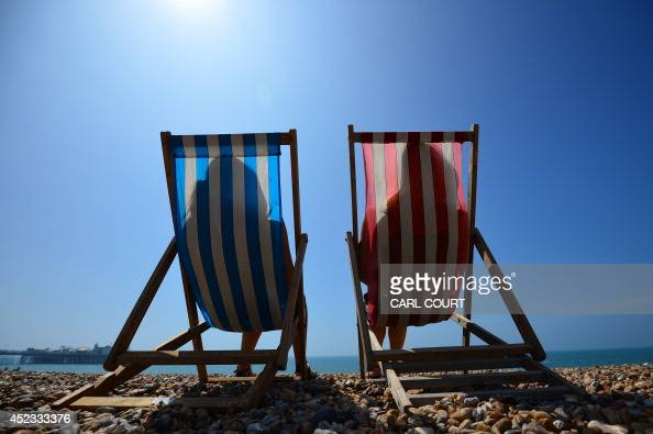 People relax in deck chairs on the beach in Brighton on July 18 as parts of the country were expected to experience the hottest day of the year so...