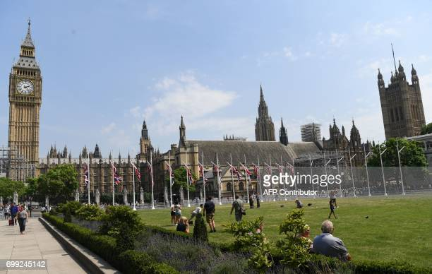 People relax in the hot weather on Parliament Square opposite the Houses of Parliament in central London on June 21 2017 Europe sizzled under a...