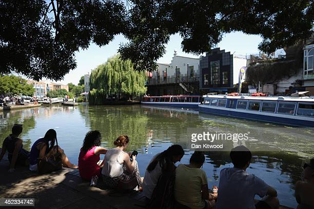 People relax in the shade of a tree next to the Regent's Canal on July 18 2014 in London England The Met Office has issued a heatwave alert as...