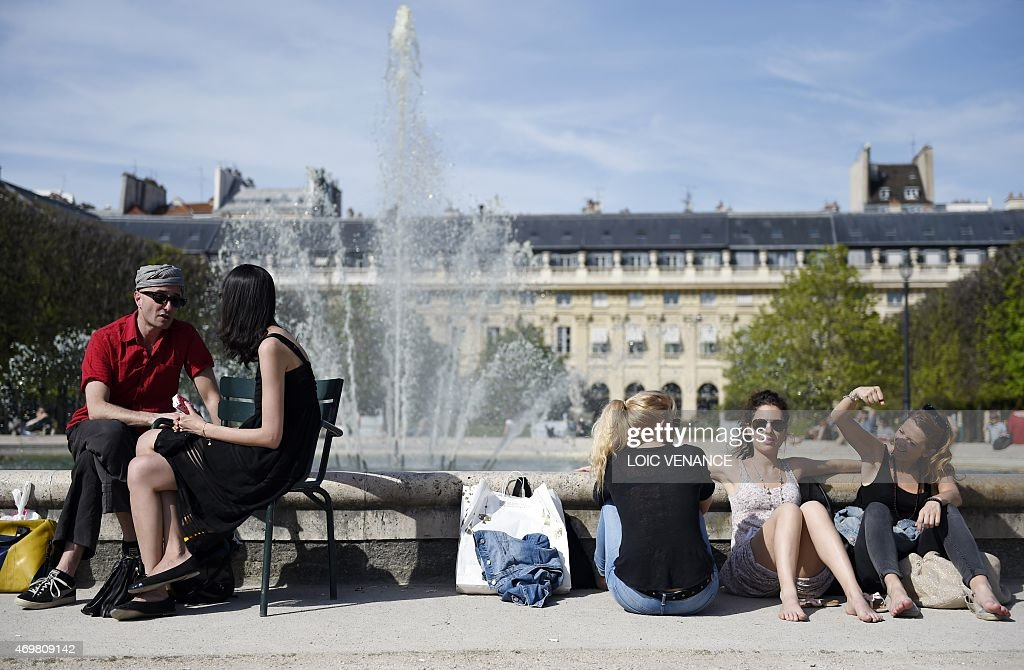 People relax in the sun in the gardens of the Palais Royal in Paris on April 15 2015 AFP PHOTO / LOIC VENANCE