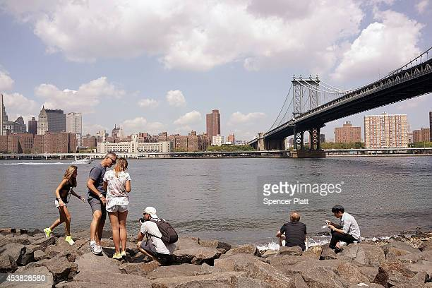 People relax near the water in DUMBO an acronym for Down Under the Manhattan Bridge Overpass on August 19 2014 in the Brooklyn borough of New York...