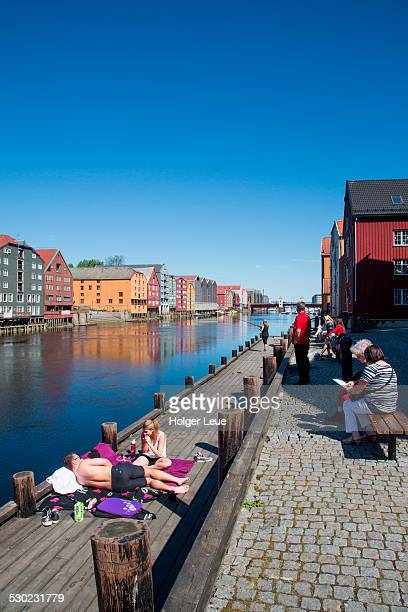 People relax near wharves along Nidelva river