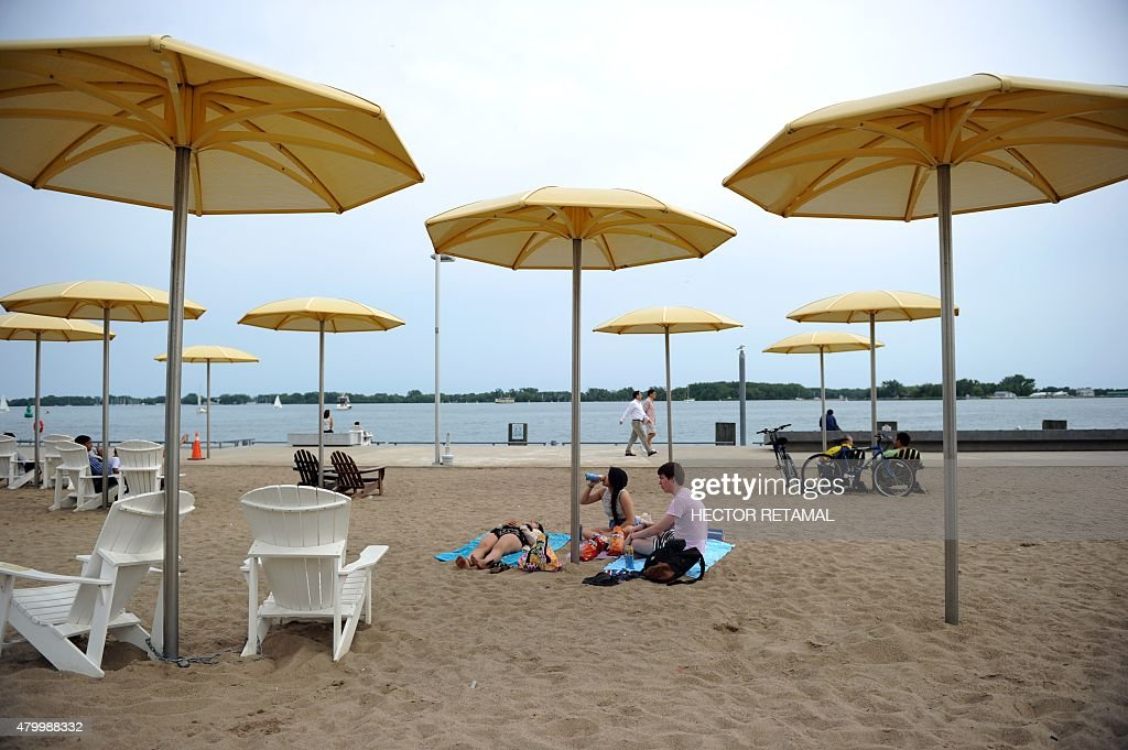 People relax on an the Urban Beach, in HTO Park in Toronto, Ontario, on July 8, 2015, two days before the opening ceremony for the 2015 Pan American Games.