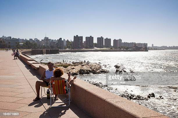 People relax on seawall and drink mate