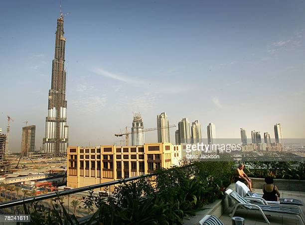 People relax on sun loungers on the roof of a residential block overlooking the site of the Burj Dubai currently the tallest building in the world on...