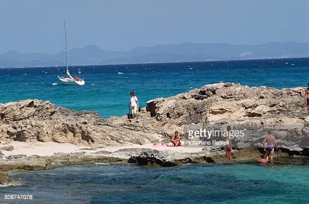 People relax on the beach and in the sea on the coast of Formentera in the Balearic Islands of Spain