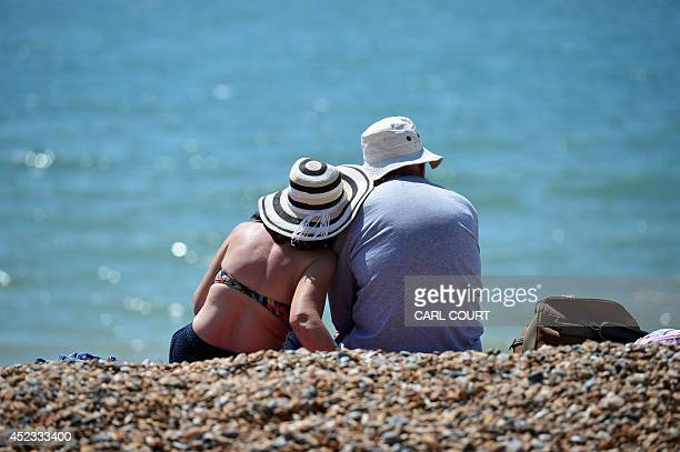 People relax on the beach in Brighton on July 18 as parts of the country were expected to experience the hottest day of the year so far and the Met...
