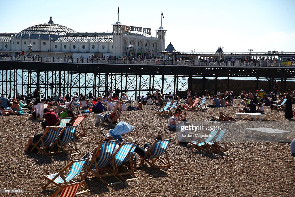 People relax on the beach in front of Brighton Pier on May 6, 2013 in Brighton, England. Visitors have flocked to Brighton Beach as the Met Office predicted the May Day Bank Holiday to be the hottest day of the year so far.