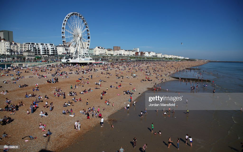 People relax on the beach in front of the Brighton Ferris Wheel on May 6, 2013 in Brighton, England. Visitors have flocked to Brighton Beach as the Met Office predicted the May Day Bank Holiday to be the hottest day of the year so far.