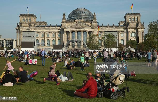 People relax on the lawn in front of the Reichstag during celebrations on the 25th anniversary of German reunification on October 3 2015 in Berlin...
