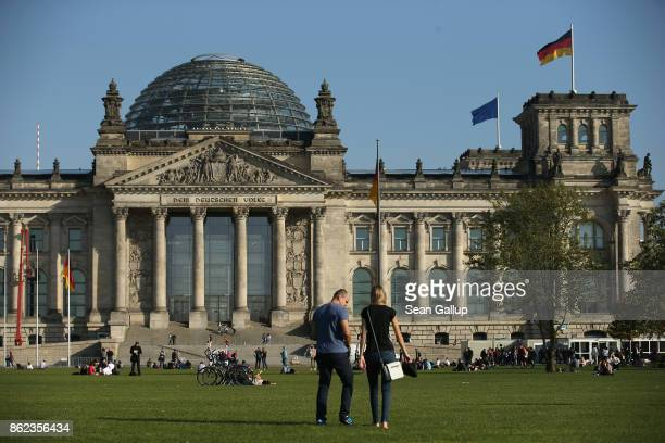 People relax on the lawn in front of the Reichstag seat of the Bundestag on October 17 2017 in Berlin Germany Following German federal elections last...