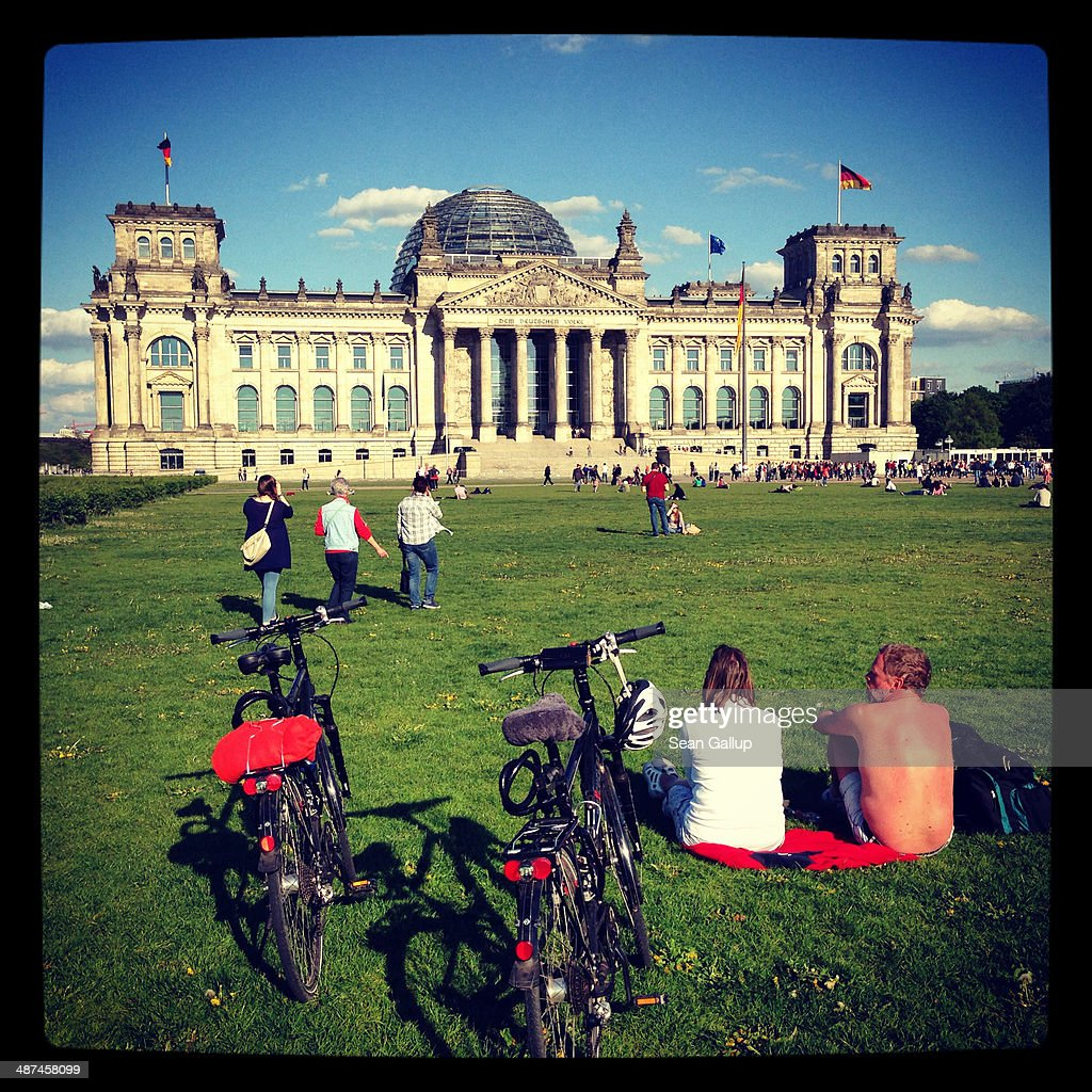People relax on the lawn outside the Reichstag on April 28, 2014 in Berlin, Germany. The Reichstag, home of the Bundestag, the German parliament, is among the city's major landmarks and a favourite tourist destination.