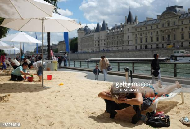 People relax on the sand during the 'Paris Plage' event on the banks of the river Seine in Paris on July 29 2015 AFP PHOTO / LOIC VENANCE
