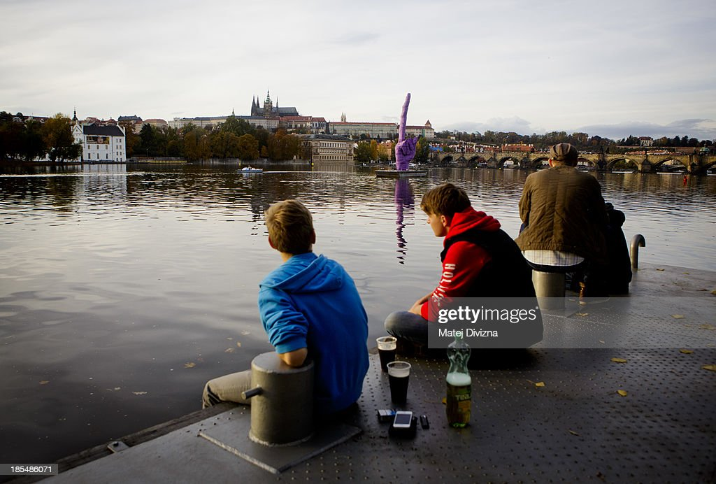 People relax with drinks on the Moldau river bank near the sculpture 'Middle Finger ' by David Cerny as it stands pointing towards Prague Castle, the seat of the Czech President Milos Zeman on October 21, 2013 in Prague, Czech Republic.