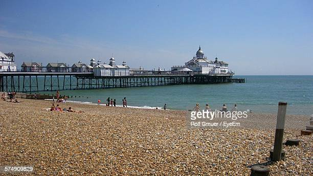 People Relaxing At Beach By Eastbourne Pier Over Sea