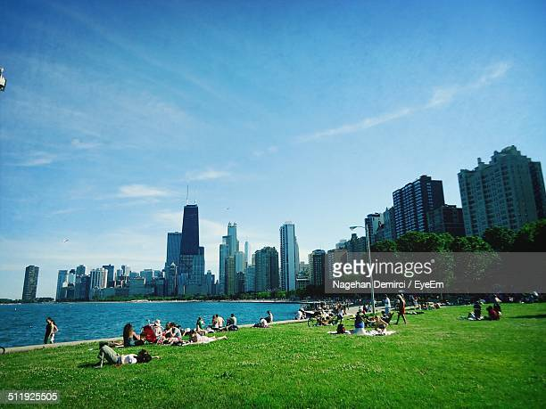 People relaxing by Lake Michigan in summer, city skyline in background