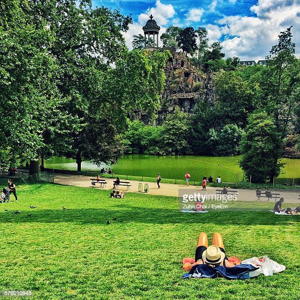 People Relaxing In Park Against Lake At Parc Des Buttes-Chaumont