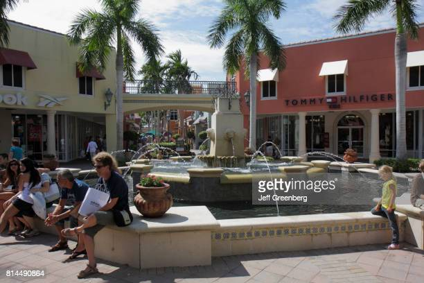 People relaxing on a fountain at Miromar Outlets