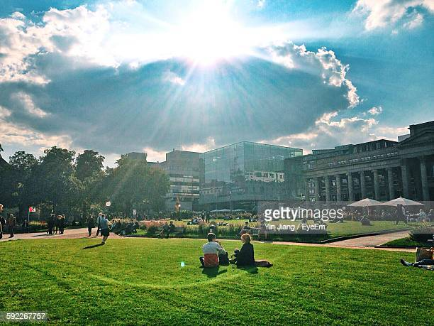 People Relaxing On Grassy Field By Buildings Against Cloudy Sky During Sunny Day
