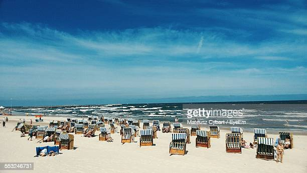 People Relaxing On Hooded Beach Chairs Against Blue Cloudy Sky
