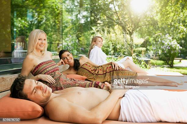 People relaxing on mattresses in spa resort