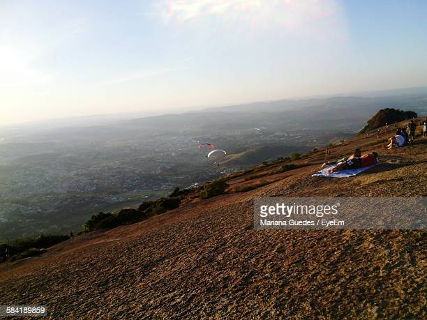 People Relaxing On Mountain Against Sky