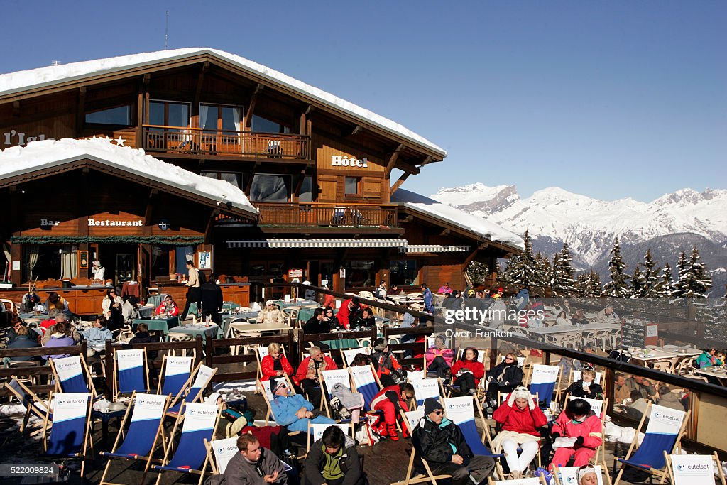 People Relaxing On Ski Lodge Patio : Stock Photo