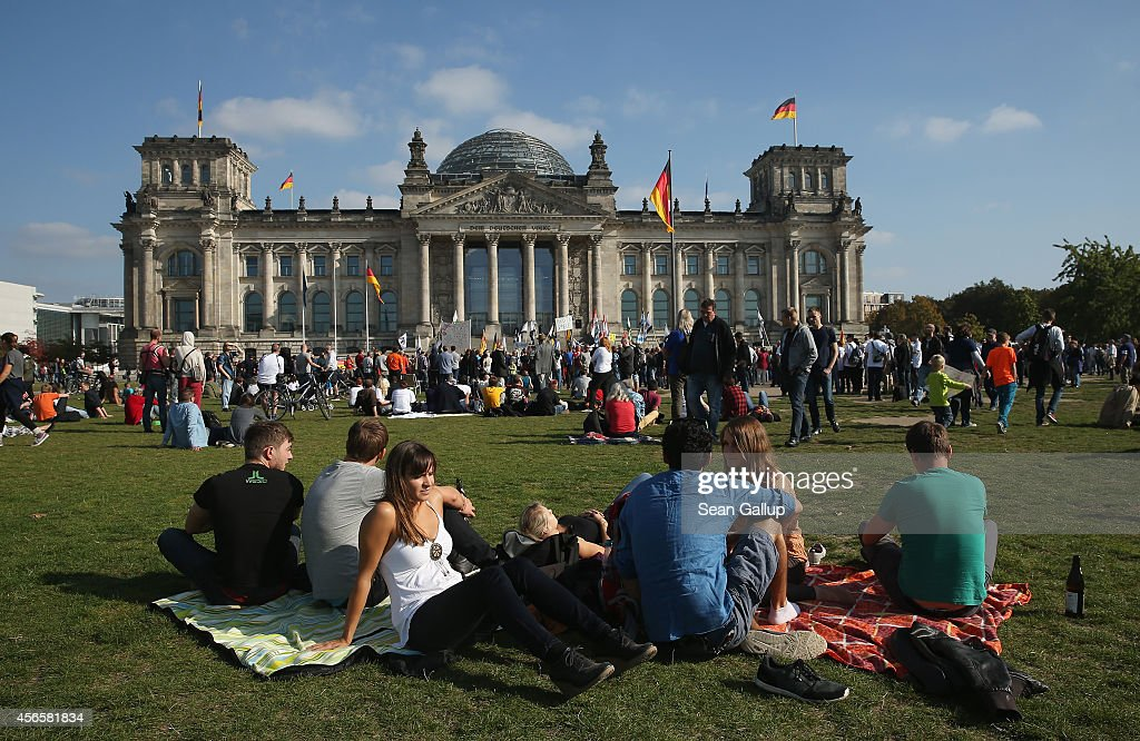 People relay on the lawn infront of the Reichstag on German Unity Day (Tag der Deutschen Einheit) on October 3, 2014 in Berlin, Germany. Germany is celebrating the 24th anniversary of the day when former West Germany and East Germany reunited into modern Germany in 1990 following the end of the Cold War. This year Germany will also celebrate the 25th anniversary of the fall of the Berlin Wall that heralded the collapse of communist authority in East Germany.