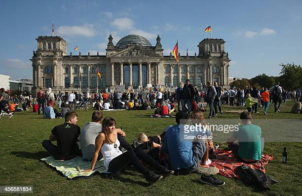 People relay on the lawn infront of the Reichstag on German Unity Day on October 3 2014 in Berlin Germany Germany is celebrating the 24th anniversary...