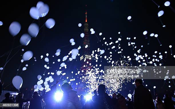 People release balloons to celebrate the New Year during an annual countdown ceremony in Tokyo on January 1 2015 Some 2000 guests of the Prince Park...