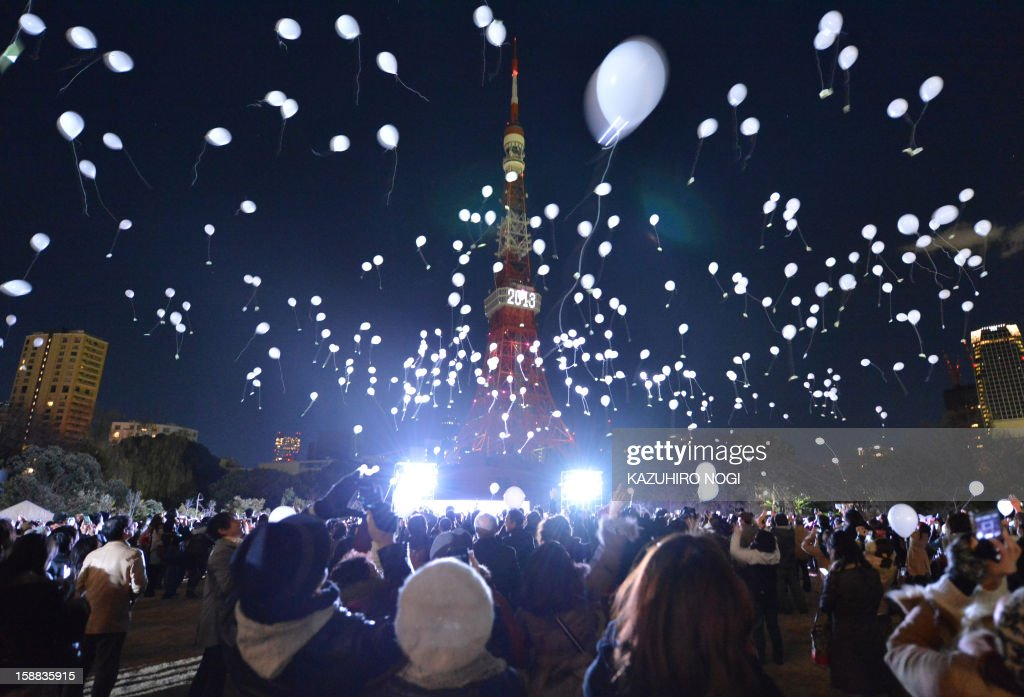 People release balloons to celebrate the New Year's during an annual countdown ceremony produced by the Prince Park Tower Tokyo, flagship of the Prince hotel chain in Tokyo on January 1, 2013. Some 1,000 balloons were released in the air with the visitors wishes. AFP PHOTO/ KAZUHIRO NOGI