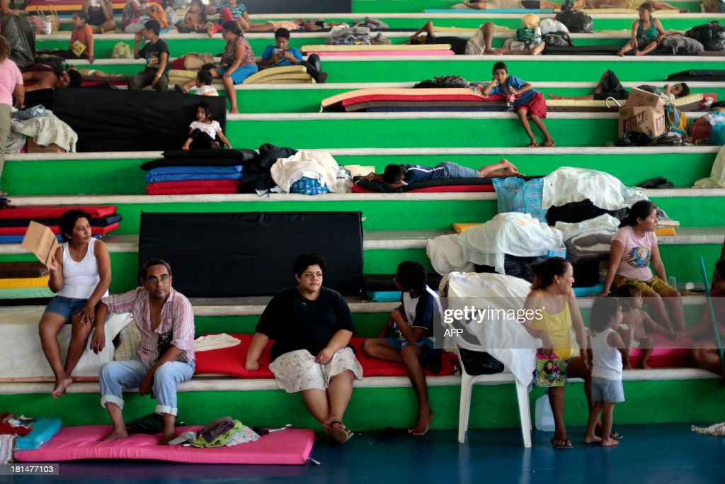 People remain at a shelter after being evacuated in Acapulco, Guerrero state, Mexico on September 21, 2013. Mexico looked Saturday to the Herculean task of rebuilding after a rare double onslaught of storms, with nearly 170 people feared dead in the path of destruction. AFP PHOTO/ Pedro Pardo