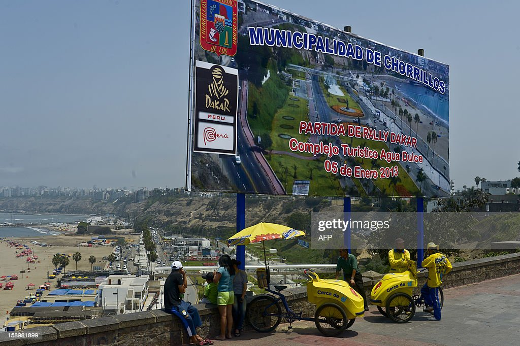 People remain near a sign advertising the 2013 Dakar Rally in Lima on January 4, 2013. This year the rally will thunder through Peru, Argentina and Chile from January 5 to 20.